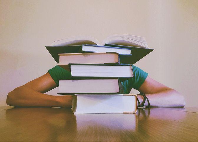 積み上げられた本の後ろで学習している人のイメージ画像